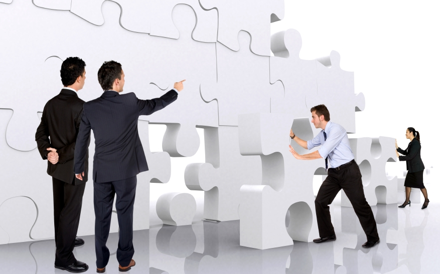 business teamwork - business men making a puzzle over a white background